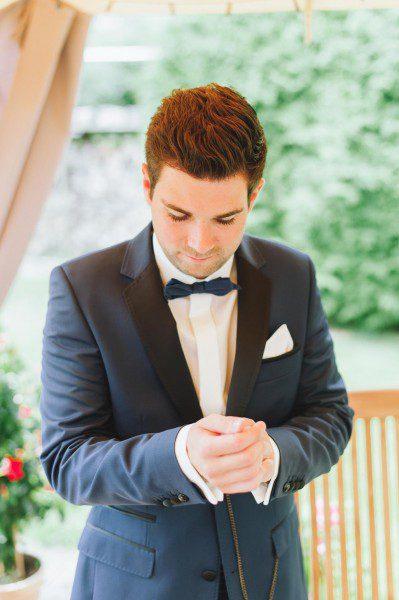 Bräutigam mit dunkelblauen Anzug mit Schleife