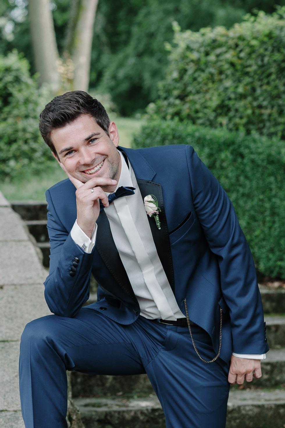 Bräutigam in dunkelblauem Anzug mit Schleife und Reversschmuck